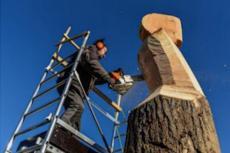L'artiste en plein travail sur une nacelle avec un tronçonneuse de 12 kg; tenue à bout de bras